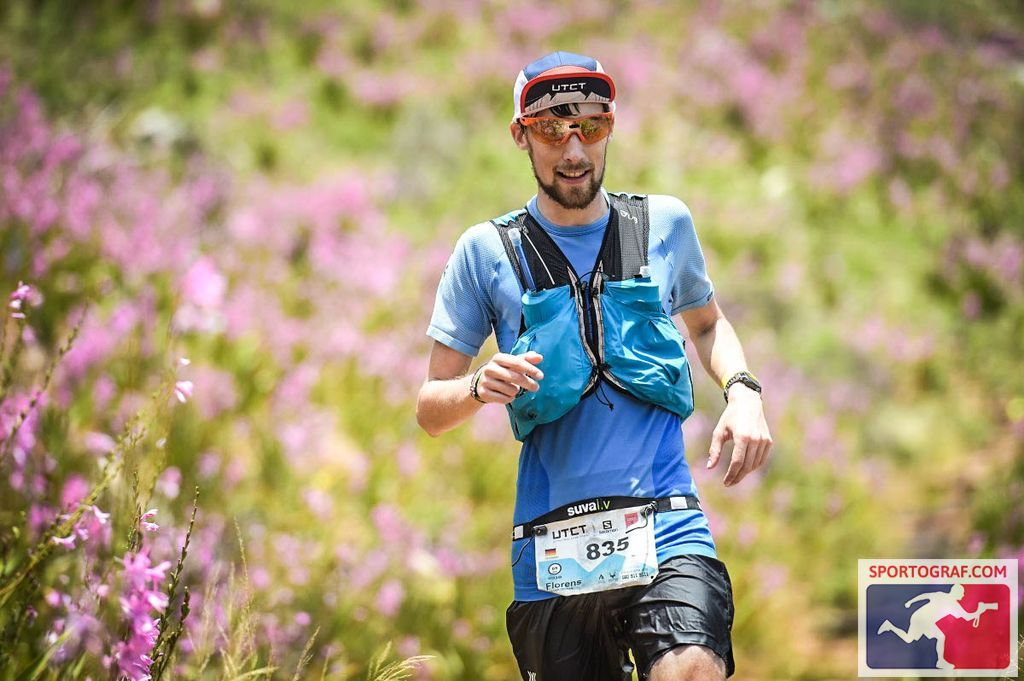 FloRuns runs through a field of pink flowers on the last downhill of the Ultra-Trail Cape Town