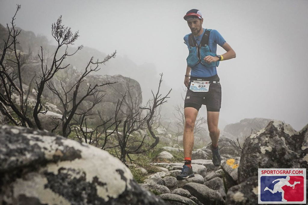 FloRuns jumping over rocks and boulders on top of the misty Table Mountain during the Ultra-Trail Cape Town